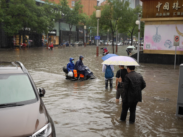 Scooter and people on a flooded street in Taiyuan, China