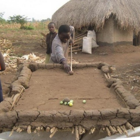 A mud and bamboo pool table with vegetables as balls!