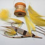 6. Materiały potrzebne do wykonania mokrej majówki:   -żółty dubbing  -szyjne pióra bkoguta i piersiowe kaczora krzyżówki barwione na żółto - złota lameta - promienie sterówki koguta bażanta łownego - haczyk z przedłużonym trzonkiem