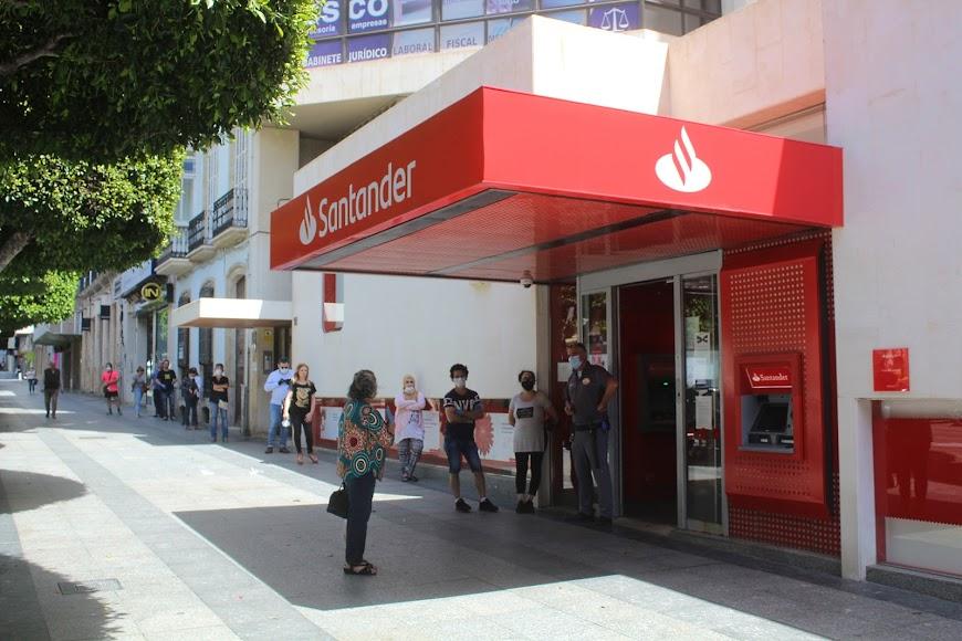 Público esperando su turno de entrada al Banco de Santander, en el Paseo de Almería.