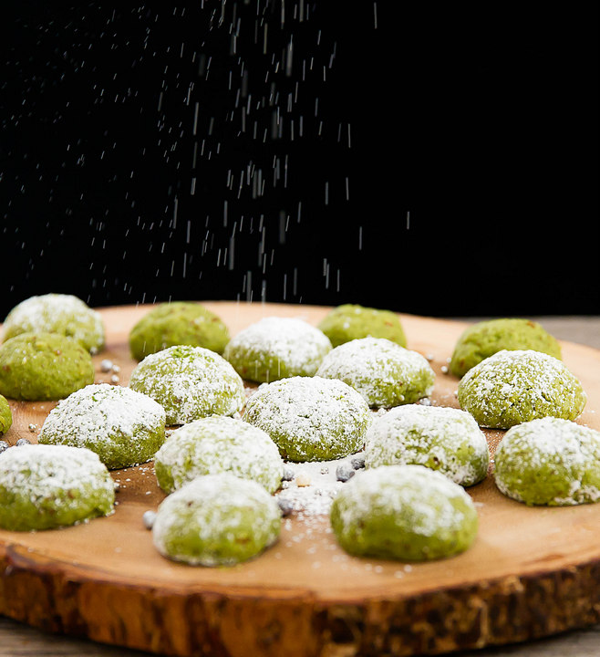process photo showing cookies being dusted with powdered sugar