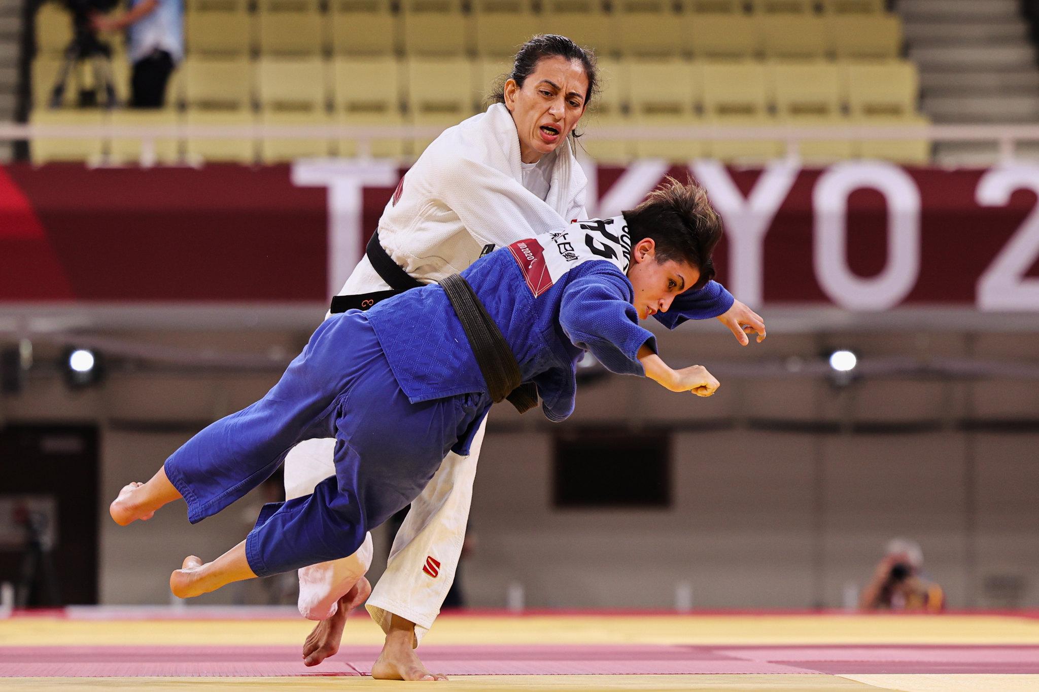 Lúcia Araújo de judogui branco derruba Laura Gonzalez que veste um jugogui azul