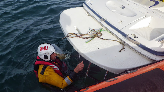 A 5.5m speedboat had picked up a pot buoy and fouled its propeller and an ILB crew member enters the water to cut it free. 1 September 2013 Photo: RNLI/Poole