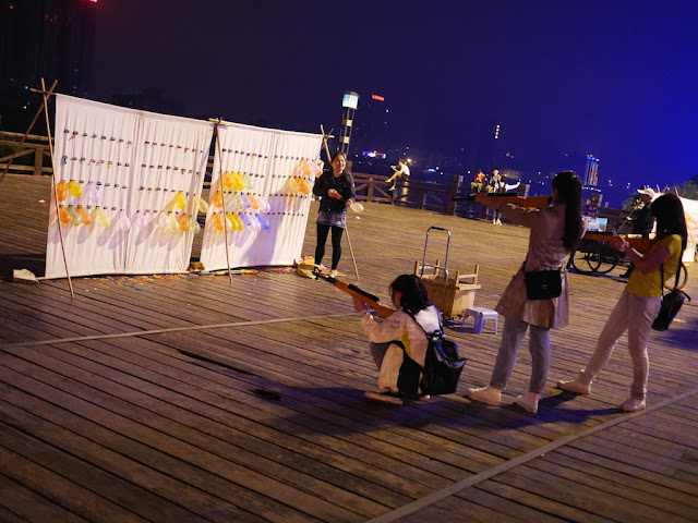 three young women shooting balloons at night in Hengyang, China