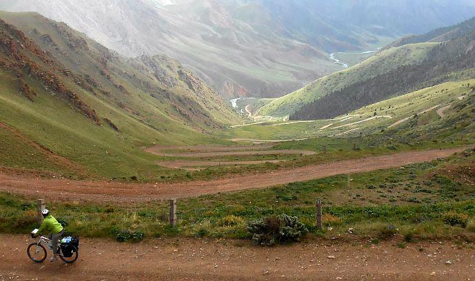 Blick von der Passhöhe Terskei-Torpok (3132 m, Тескей-Торпок, Тридцать три Попугаи, Tridzat Tri Popugai, 33 попугая) auf die 33 Serpentinen, die zum Song-Köl(-Wasserfall) hinabführen, Kirgistan