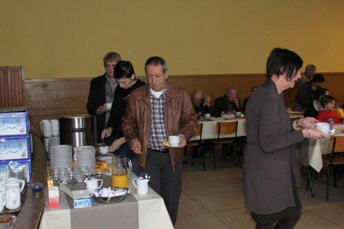 De eerste mensen stromen toe en worden ontvangen met koffie en cake.