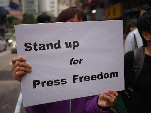 "Woman holding a sign saying ""Stand up for Press Freedom"" at a rally in Hong Kong"