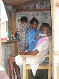 A villager gets a shave at the roadside barber's
