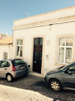 Et lite murhus ved en brolagt gate.