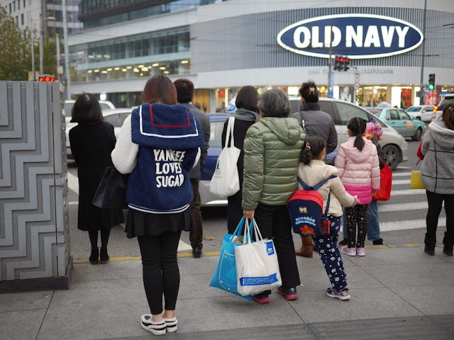 "Young woman wearing a ""YANKEE LOVES SUGAR"" coat with Old Navy in the background in Shanghai"
