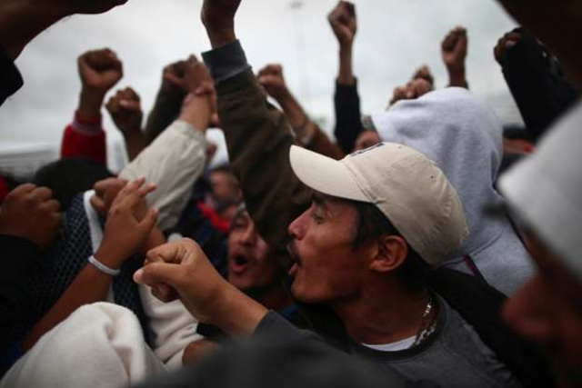 Members of a caravan of migrants from Central America, celebrate near the San Ysidro checkpoint as the first fellow migrants entered U.S. territory to seek asylum on Monday, 1 May 2018, in Tijuana. Photo: Edgard Garrido / REUTERS
