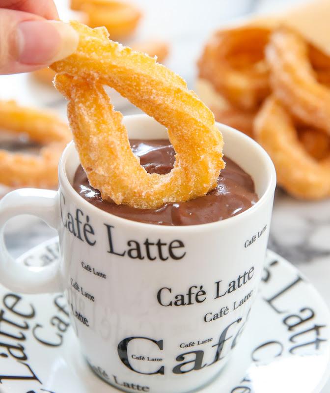 close-up photo of a mug of chocolate with a churro