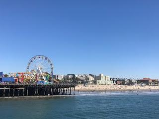 Pariserhjul på en brygge. En strand sees i bakgrunnen.