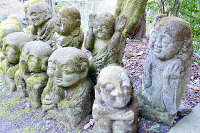 Otagi Nenbutsuji Temple features 1200 stone sculptures of rakan, the Buddha's disciples, all with different facial expressions and poses. Is the one in the back playing peek a boo?