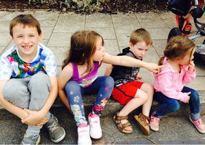 Four children sitting on the curb waiting for the Teignmouth Carnival procession