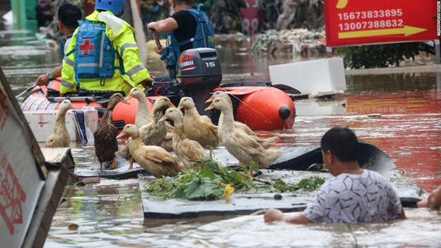 Rescue workers helping people on a flooded street in Loudi, Hunan province, in July 2017. Photo: CNN