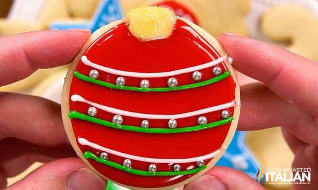 holding up a decorated sugar cookie