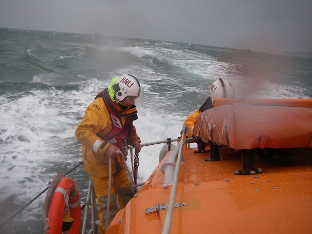 23 September 2012 - rough weather ALB training exercise in Poole Bay. Checking the tripping line before feeding out the drogue. Photo credit: Poole RNLI/Dave Riley.