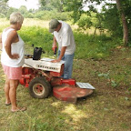 George uses Owen's mow as a tool bench to drill holes in signs.
