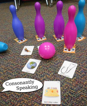 Plastic bowling pins on top of articulation cards knocked over with cards word side up