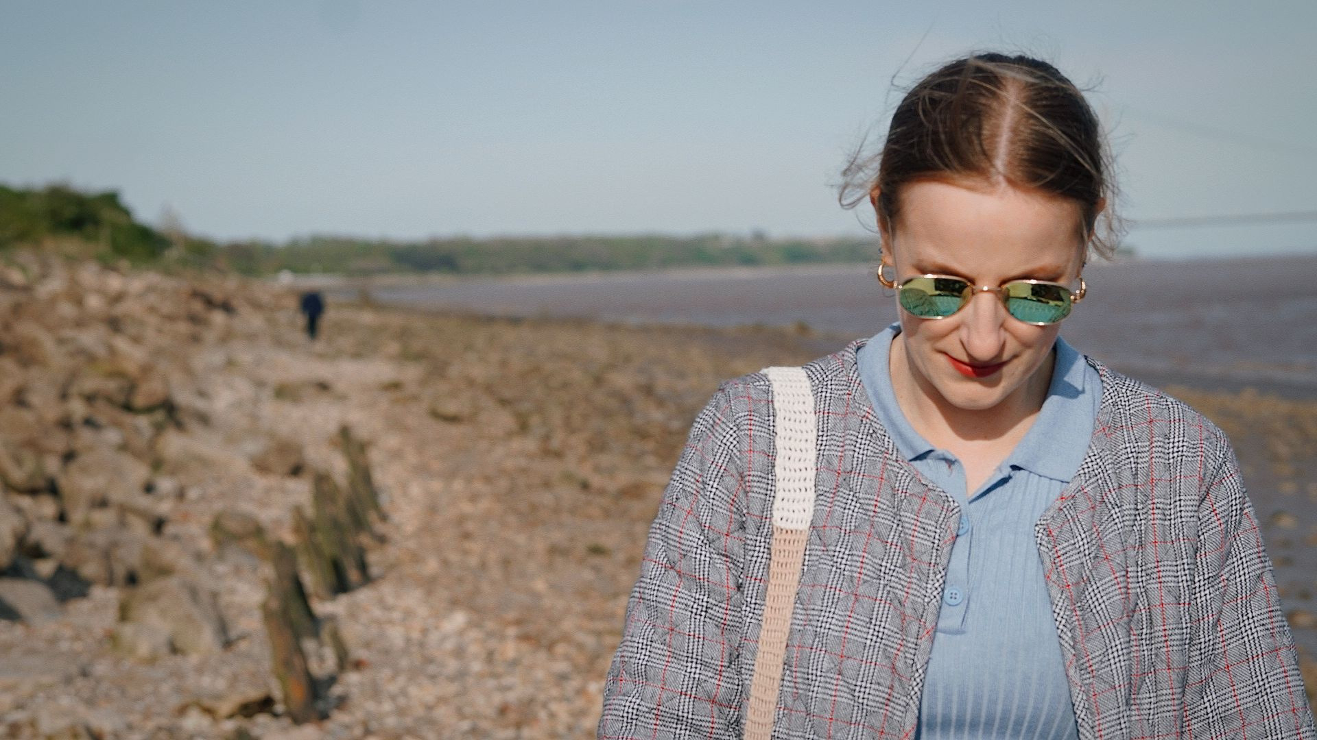 A girl with her head down walking along North Ferriby Foreshore.