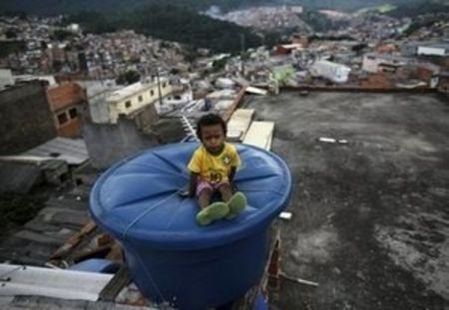 Igor, 6, sits on a water container, on the roof of his house in Brasilandia slum, in Sao Paulo, Brazil, 10 February 2015. Nacho Doce / REUTERS