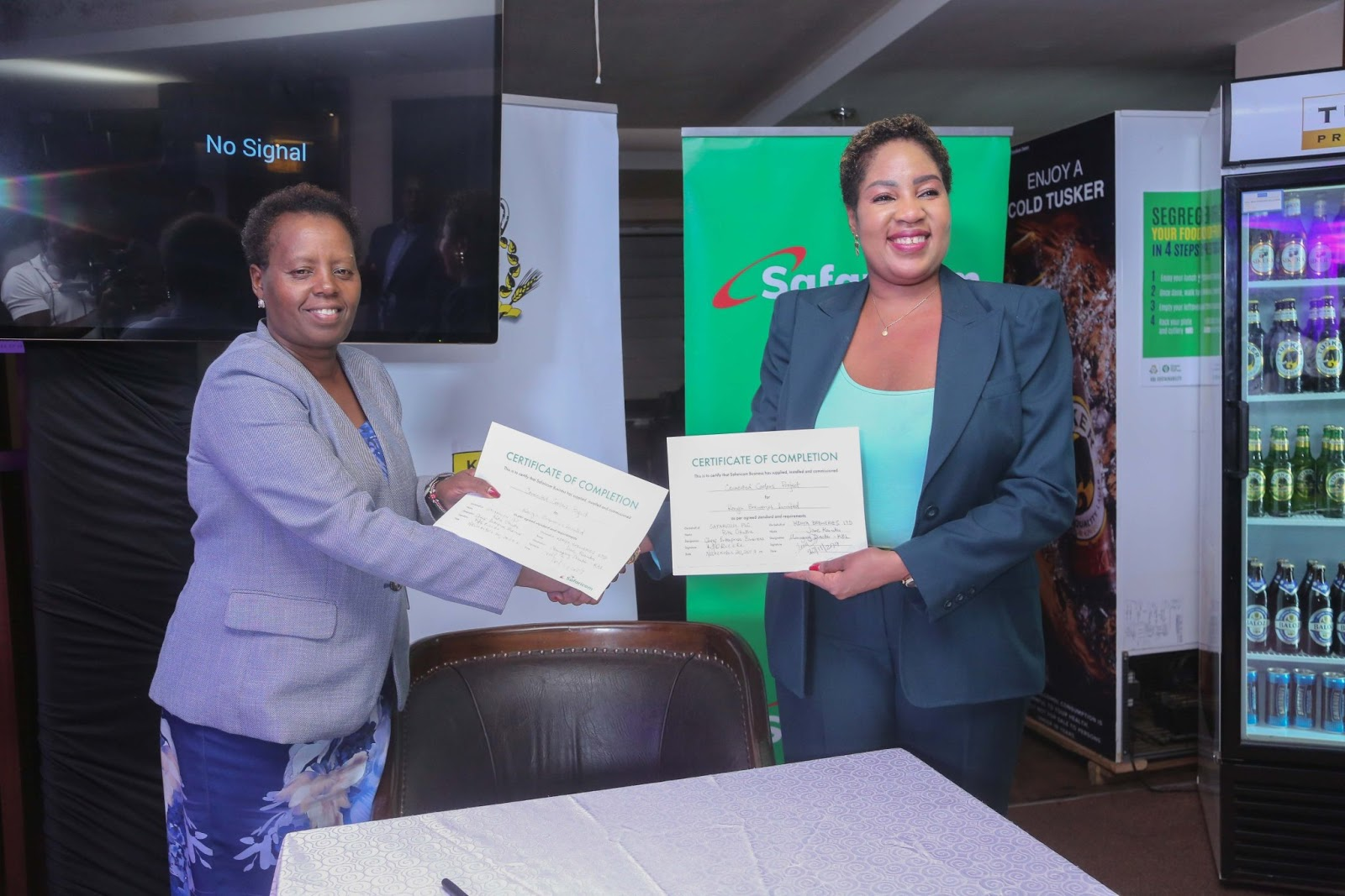 Safaricom manager hands C2B scripts to the EABL manager.