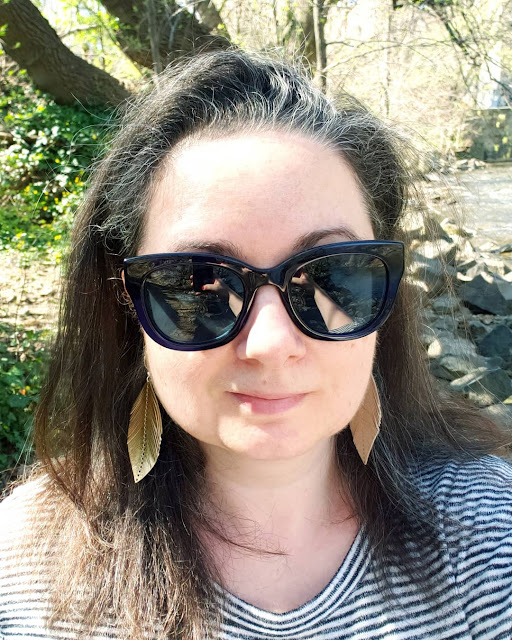 Woman in sunglasses and leather earrings