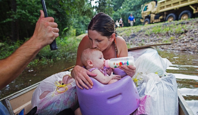 Danielle Blount kisses her 3-month-old baby Ember as she feeds her while they wait to be moved by members of the Louisiana Army National Guard near Walker, after historic flooding in August 2016. Photo: Max Becherer / Associated Press