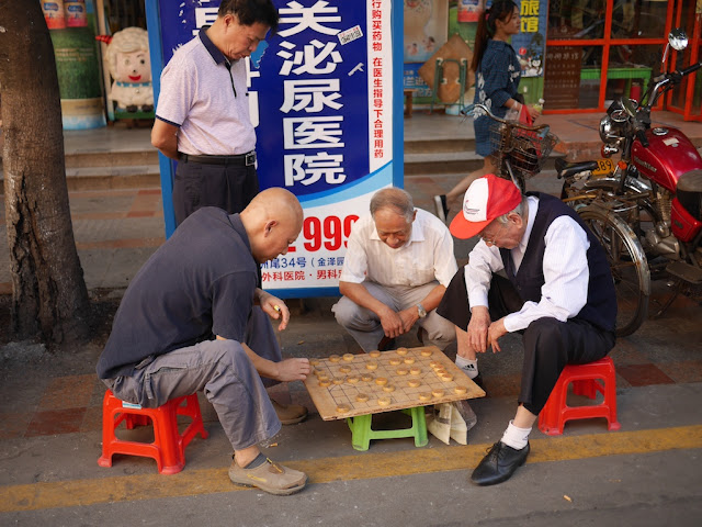men playing and watching a game of xiangqi on the side of a road in Shaoguan, Guangdong