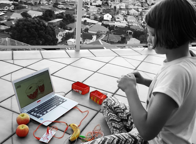 Black and white photo (with colour elements) of girl on balcony with a Makey Makey set