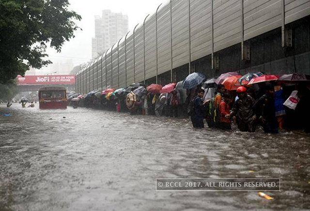 People walk through flooded street during heavy rain showers in Mumbai on Eastern express highway near Kingcircle station, 30 August 2017. Photo: BCCL / India Times