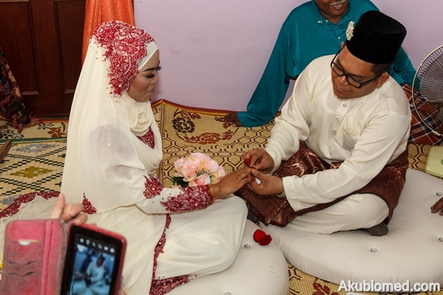 pengantin lelaki sarung cincin ke jari pengantin perempuan