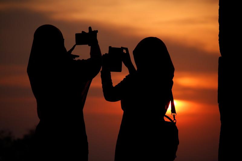 Dos chicas haciendo fotos en el atardecer de Ratu Boko