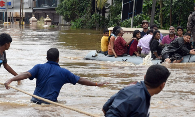 Volunteers and rescue personnel evacuate local residents in an Indian Navy boat from a residential area in Aluva, Kerala, on 17 August 2018. Photo: RK Sreejith / AFP / Times of India