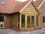 Green Oak garden room with stained softwood Dooset and windows inserted