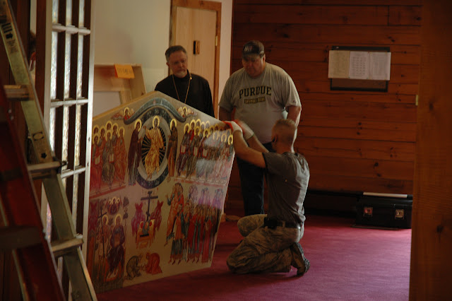 Construction workers from the team led by Miroslav Borowski discuss the mounting procedure with Fr. John and Dave Whitehorn.