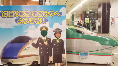 I pose as a conductor with a bunch of models of shinkansen while waiting for the time to board our bullet train to Nagano
