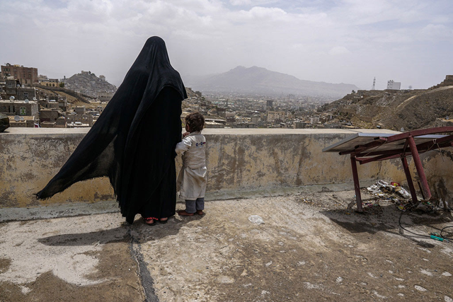 An internally displaced woman and her daughter look over the city of Sana'a, Yemen, from the roof of this dilapidated building they call their new home. Photo: Giles Clarke / UN OCHA