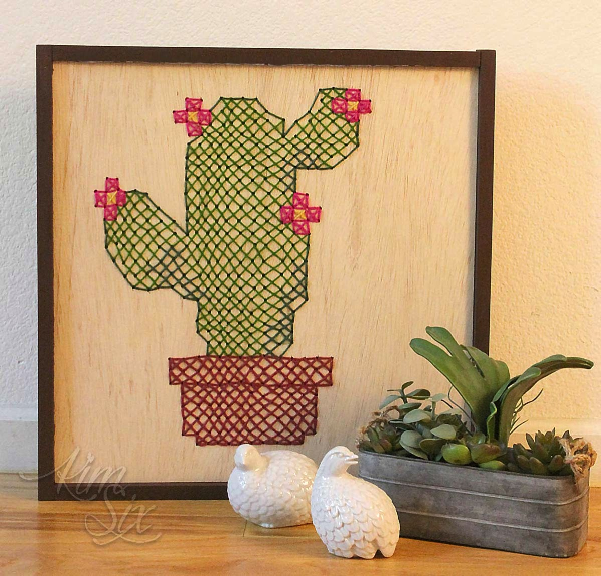 Cross stitched cactus on plywood