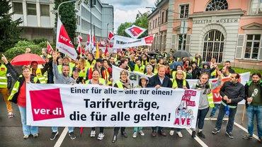 Streikende mit verdi-Fahnen und Tranparent: «Tarifverträge, die für alle gelten!».