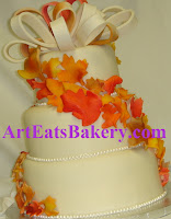 Three tier custom ivory fondant wedding cake with pearls, elegant edible orange, yellow and brown fall leaves cascade design and bow topper