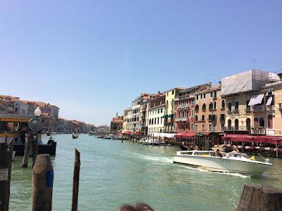 Canal Grande i Venezia. En bred kanal med gamle palasser på begge sider. En motorbåt er på vei ut av bildet.