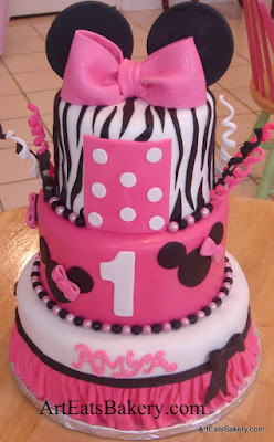 Three tier Minnie Mouse creative fondant birthday cake design with mouse ears, bow, zebra stripes, edible pearls, and skirt
