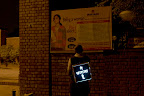 in front of a delhi police poster about safety at night-time for girl students