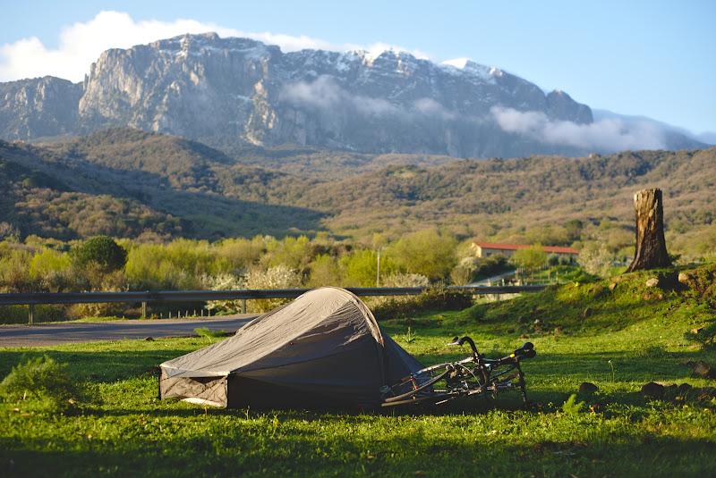 Locul de cort din prima noapte, cu iarba verde, liniste si munti inzapeziti in distanta.