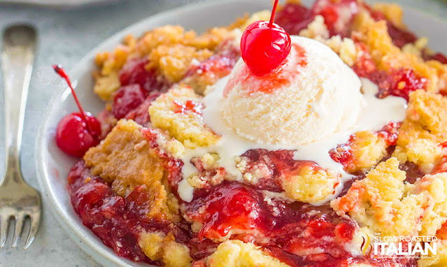 cherry dump cake with a scoop of vanilla ice cream melting over the hot cake