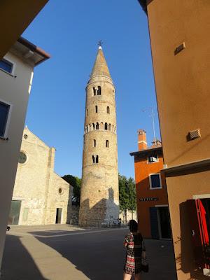 Et torg med et frittstående rundt og litt skjevt tårn. En kirke synes delvis i bakgrunnen.