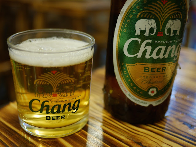 "small Chang Beer glass next to a Chang Beer bottle with ""Product of Thailand"" on the label"