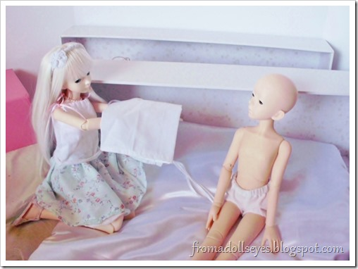 Putting a dress on a male doll.  He needs to wear something.